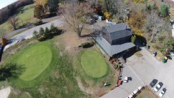 This is the Locust Valley clubhouse from 125' up with a view of the clubhouse, practice green and second green.